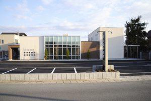 鉄骨造の医院 カーテンウォールとジョリパット塗の外壁とシンプルな箱型の建物です