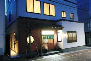 老舗の鍋料理屋おまつ外観 入口部分の朱色の塗り壁と瓦の飾り庇が和のお店の印象を表します